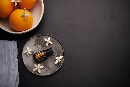doTERRA Citrus Bliss with orange blossom flowers on a ceramic plate with a white ceramic bowl filled with seville oranges and orange blossoms on a black concrete background.