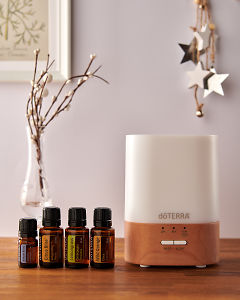 doTERRA Lumo diffuser with Juniper Berry, Citrus Bliss, Lemongrass and Wild Orange essential oils and holiday decorations on a side table.