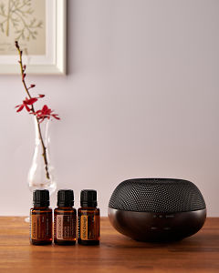 doTERRA Brevi Walnut diffuser with Cassia, Cedarwood and Wild Orange essential oils on a side table.