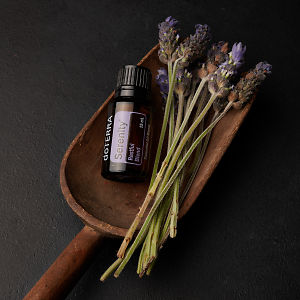doTERRA Serenity with lavender flowers in a wooden scoop on a black concrete background.
