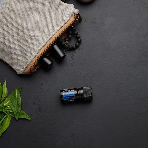 doTERRA Deep Blue with clutch, accessories and mint leaves on a black concrete background.
