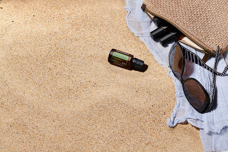 doTERRA Coriander with sunglasses, scarf and roller bottles in a clutch on the beach.