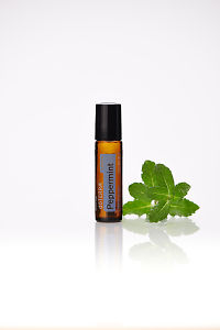 doTERRA Peppermint Touch and peppermint leaves on a white background with reflection.