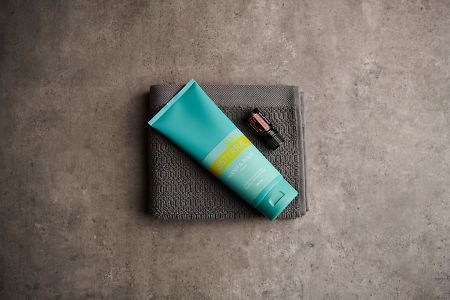 doTERRA Spa Hand and Body Lotion with Arborvitae essential oil on a gray washcloth on a stone background.