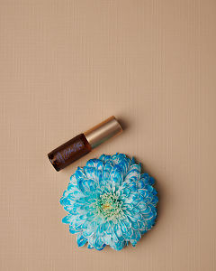 doTERRA Blue Lotus Touch 4ml and a blue flower on a tan linen textured background.