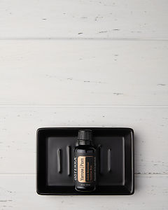 doTERRA Yarrow|Pom in a black soap dish on a white wooden background.