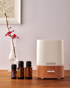doTERRA Lumo diffuser with Juniper Berry, Citrus Bliss and Frankincense essential oils on a side table.
