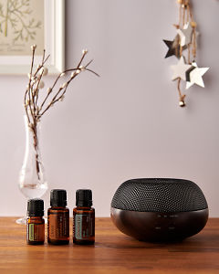 doTERRA Brevi Walnut diffuser with Cardamom, Clove and Siberian Fir essential oils and holiday decorations on a side table.