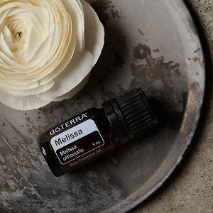 doTERRA Melissa and a white flower on a ceramic plate on a grey stone background.