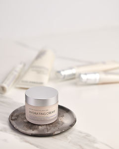 doTERRA  Hydrating Cream on a ceramic plate with other Essential Skin Care products in the background on a white marble background.