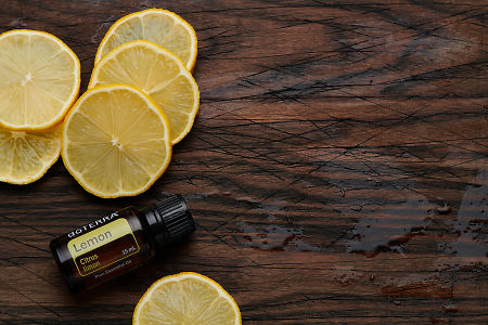 doTERRA Lemon oil and slices on rustic wooden chopping board.