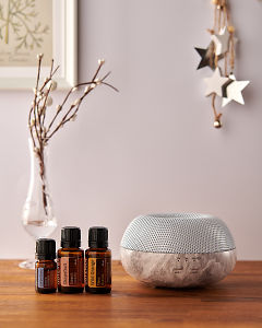 doTERRA Brevi Stone diffuser with Juniper Berry, Grapefruit and Wild Orange essential oils and holiday decorations on a side table.