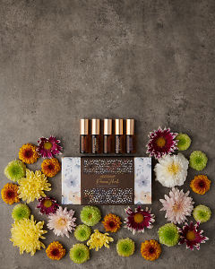doTERRA Precious Florals Collection featuring Neroli Touch, Jasmine Touch, Rose Touch, Magnolia Touch and Blue Lotus Touch with scattered flowers on a gray stone background.