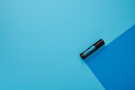 doTERRA Peace Touch on a dark blue and light blue geometric background.