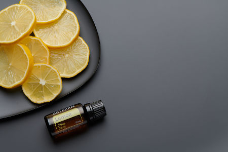 doTERRA Lemon oil and lemon slices on black melamine plate with dark grey background.