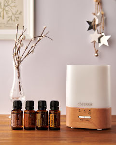 doTERRA Lumo diffuser with Cedarwood, Frankincense, Myrrh and Wild Orange essential oils and holiday decorations on a side table.