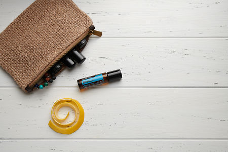 doTERRA Breathe Touch, lemon peel and clutch with oils on white wooden background.