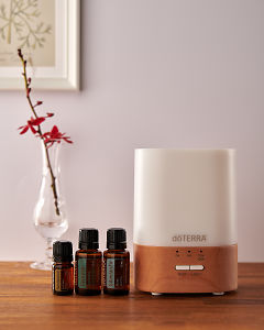 doTERRA Lumo diffuser with Sandalwood, Cypress and Siberian Fir essential oils on a side table.