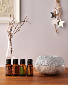doTERRA Brevi Stone diffuser with Cedarwood, Frankincense, Rosemary and Wild Orange essential oils and holiday decorations on a side table.