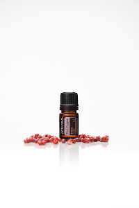 doTERRA Pink Pepper with pink peppercorns on a white background with reflection.