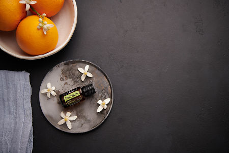 doTERRA Petitgrain with orange blossom flowers on a ceramic plate with a white ceramic bowl filled with seville oranges and orange blossoms on a black concrete background.