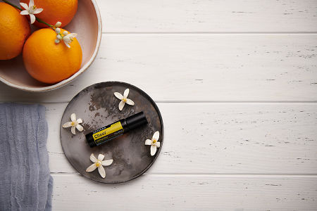 doTERRA Cheer Touch with orange blossom flowers on a ceramic plate with a white ceramic bowl filled with seville oranges and orange blossoms on a white wooden background.