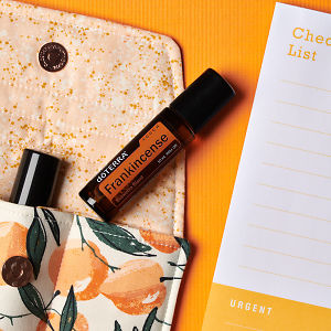 doTERRA Frankincense Touch on an essential oil bag with a check list on an orange textured background.