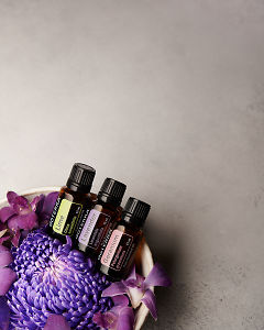 doTERRA Lime, Lavender and Geranium in a bowl of purple flowers on a pale gray background.