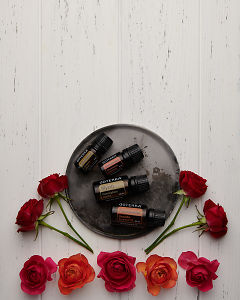 doTERRA Sandalwood, Cinnamon Bark, Myrrh and Frankincense on a ceramic plate with orange and red roses on a white wooden background.